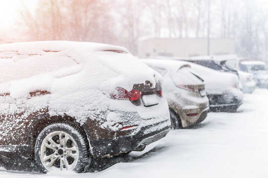Cars parked in row at outdoor parking in winter. Vehicles covered by snow during heavy snowfall. snowstorm or blizzard weather forecast