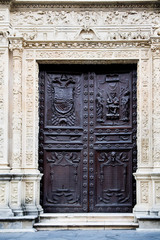 Entrance door of an ancient building with elegant wrought decorations