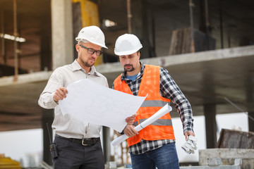 Male architect and developer discussing blueprints at construction site