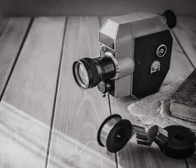Vintage old movie camera and film reels on a wooden table, old book, clothl. Retro photo. Copy space