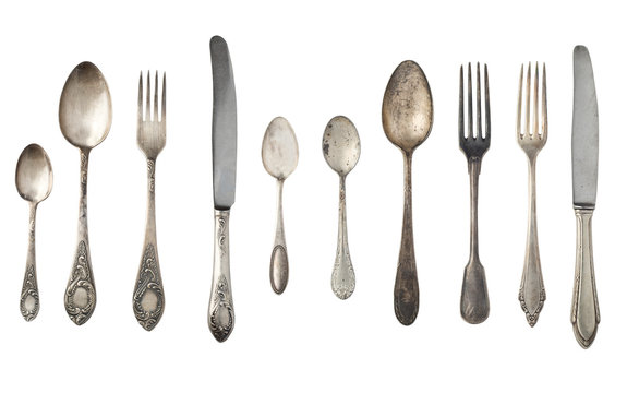 Vintage spoons, forks and knives isolated on a white background. Retro silverware.