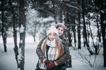 young couple in love are walking in the snowy winter forest. Positive beautiful lovers in clothes for the cold time.