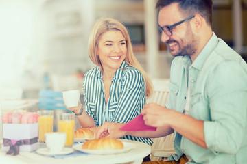 Happy loving couple enjoying breakfast in a cafe