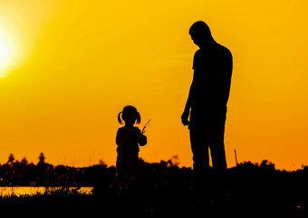 Father and Daughter in sunset background