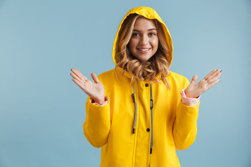 Image of joyful woman 20s wearing yellow raincoat looking at camera, isolated over blue background