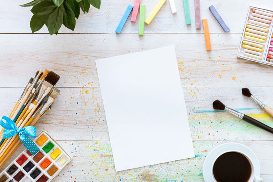 Creative workplace for painting concept, paint brushes, paintbox with watercolors, crayons, coffee and blank album paper on white wooden artistic background. Top view with copy space, flat lay