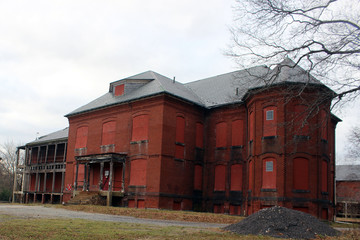 Boarded up and abandoned brick mental hospital asylum building