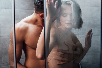 handsome man passionately embracing and holding woman in shower