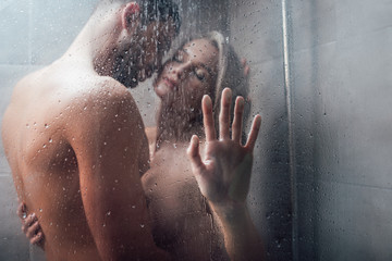 affectionate man passionately embracing beautiful woman in shower