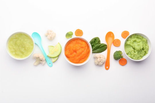 Flat lay composition with healthy baby food on white background