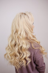 Back view of blonde with long luxurious curls.