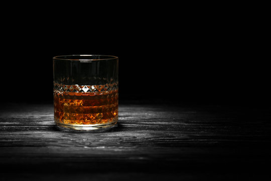 Glass of whisky with ice on wooden table against black background