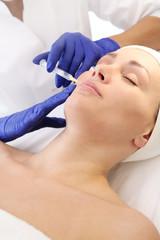 Ostrzykiwanie kwasem hialuronowym. Pacjentka w klinice kosmetycznej, kosmetyczka wykonuje zabieg ostrzykiwania.