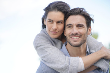 Portrait of gorgeous couple outdoors piggybacking