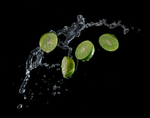 Limes with water splash or explosion flying in the air isolated on black background