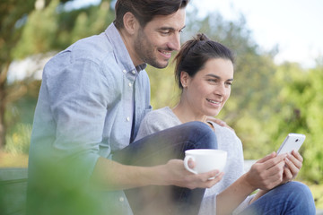 Relaxed young couple sitting together outside with mug and cellphone