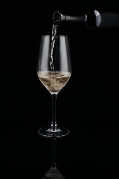 Pouring of white wine from bottle into glass on dark background