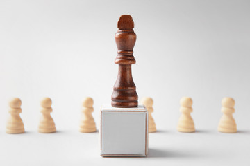 Chess piece with cube on light background