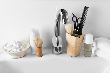 Shaving accessories with cosmetics for men on sink in bathroom