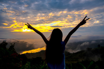 Silhouette of freedom girl in sunrise at the mountain background.