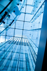 Modern glass building seen through glass ceiling.