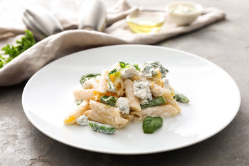 Plate with tasty penne pasta on grey table