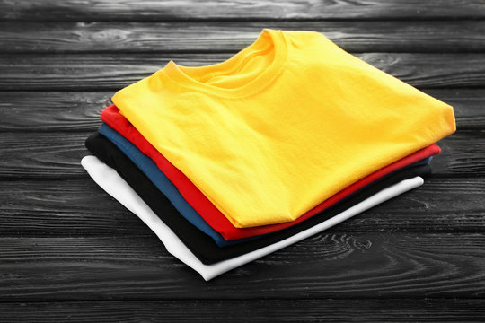 Stack of colorful t-shirts on wooden background