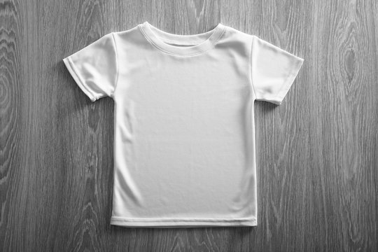 Blank white t-shirt on wooden background