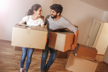 Young couple carrying big cardboard full of home essentials into a new home.Moving house.Real estate concept.