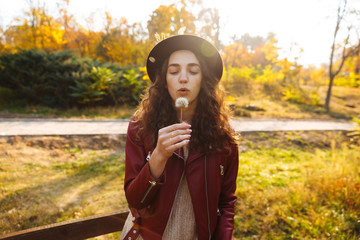 Young curly woman walking in the autumn park holding dandelion.