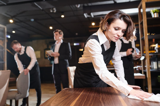 Serious busy young waitress and her colleagues preparing restaurant for open and making cleanup: she wiping wooden table with cloth