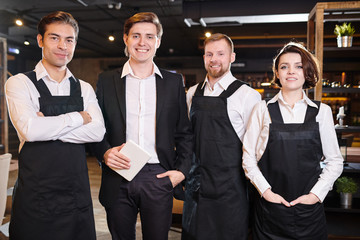 Team of restaurant professionals in ahead of manager standing in line and smiling at camera