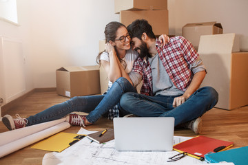Young couple moving into a new house.They sitting on floor and calculate savings and home budget.