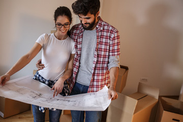 Young couple moving into a new house.They unpacking and planing to decorate new home.
