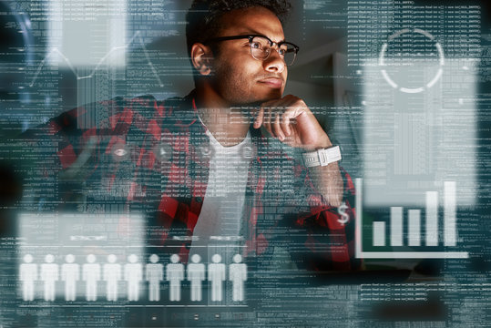 Young concentrated indian SEO specialist looking over advertising conversion