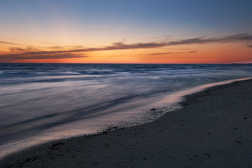 Yellow, orange and blue colors in twilight after sunset illuminate the sky and shiny, silky water along Barefoot Beach, Florida at twilight.