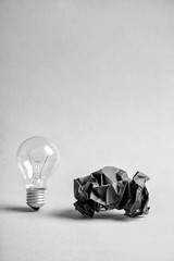 Light bulb with crumpled paper on white background
