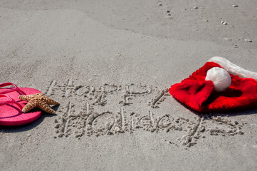 Tropical Christmas at the beach, with happy holidays written in the sand, flip flops, a starfish and santa hat.