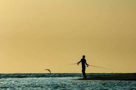 A silhouetted man fishes at sunset along Barefoot Beach, Florida.