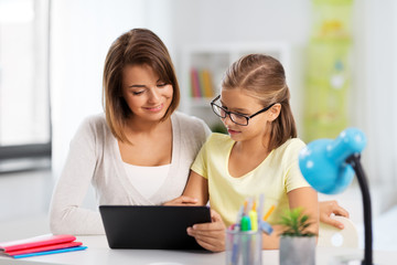 education, family and learning concept - mother and daughter with tablet pc computer doing homework together at home