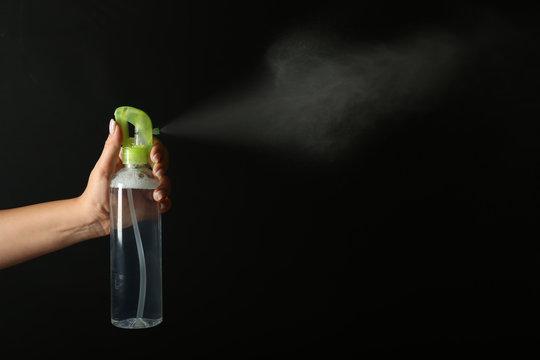 Woman spraying air freshener on dark background