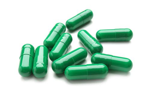 Spirulina capsules on white background