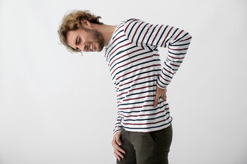 Young man suffering from back pain on light background