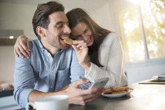 Gorgeous fun couple feeding eachother cookies in modern kitchen