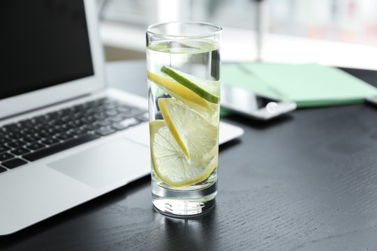 Glass of water with citrus fruits on dark table
