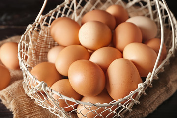 Basket with raw chicken eggs on wooden table