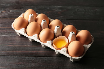 Cracked and whole chicken eggs in carton pack on dark wooden table
