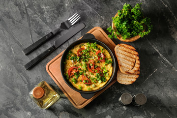 Pan with tasty omelet on grey table