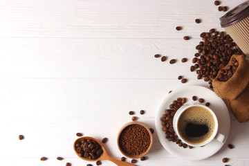 Cup of aromatic coffee and coffee beans on wooden background. Top view. Coffee drink