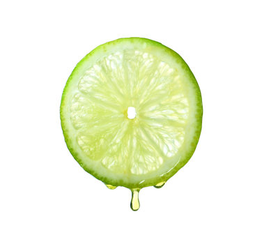 Essential oil dripping from lime slice on white background